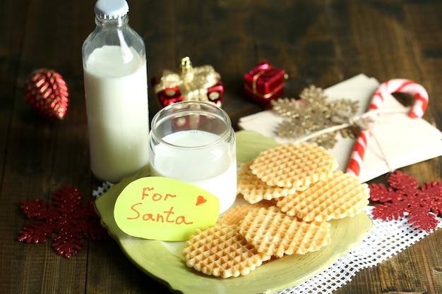 サンタさんのためのクッキーとミルク。木製の背景で