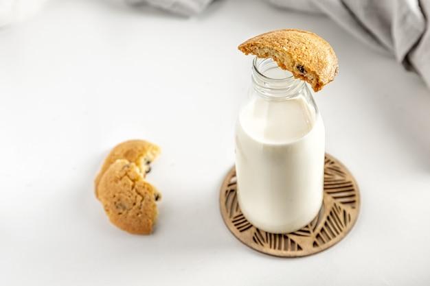 ナプキンと白いテーブルの上のボトルのクッキーとミルク