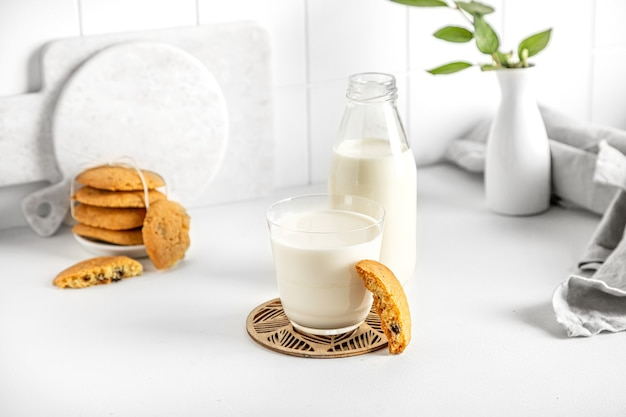 ナプキンと小さな花瓶と白いテーブルの上のガラスとボトルのクッキーとミルク