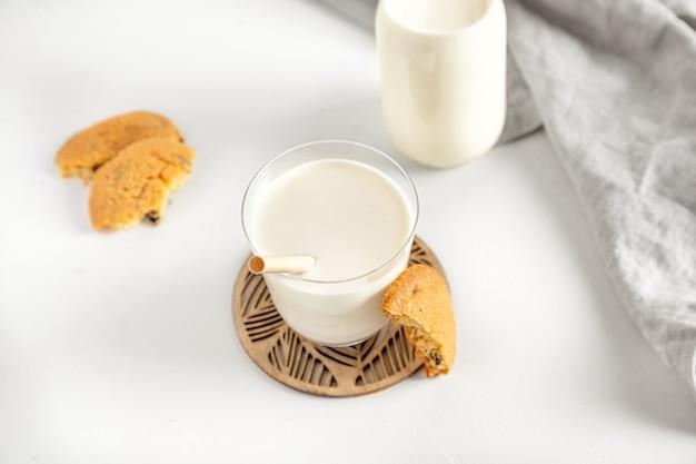 ナプキンと白いテーブルの上のガラスとボトルのクッキーとミルク