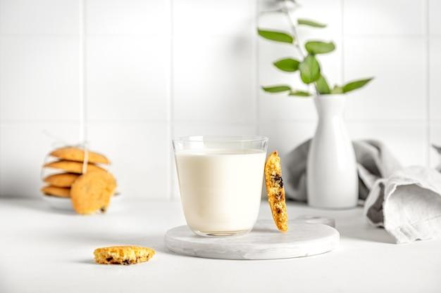 ナプキンと小さな花瓶と白いテーブルの上のガラスのクッキーとミルク