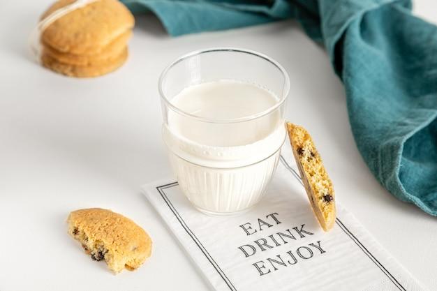 ナプキンと白いテーブルの上のガラスのクッキーとミルク