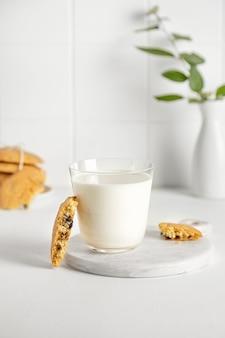 小さな花瓶と白いテーブルの上のガラスのクッキーとミルク