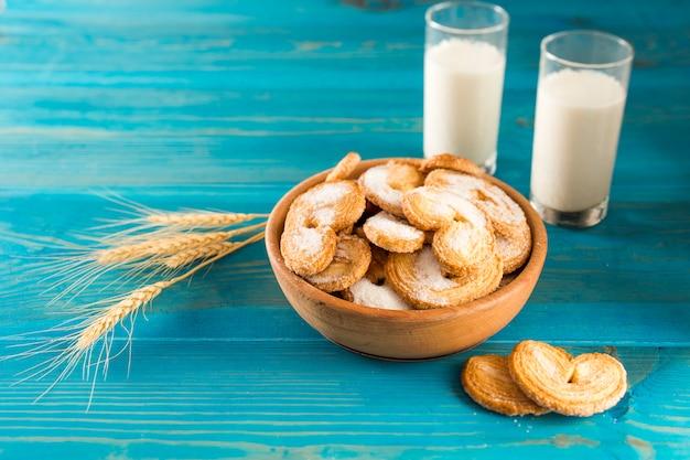 テーブルの上の小麦の穂の近くのクッキーと牛乳