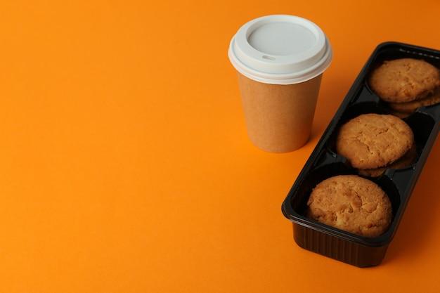 オレンジ色の背景にクッキーとコーヒーの紙コップ。