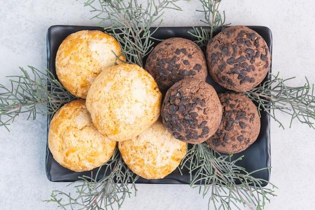 Печенье и сосновый бранч на блюде, на мраморе.