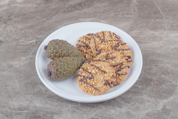 Печенье и шишки на блюде на мраморе