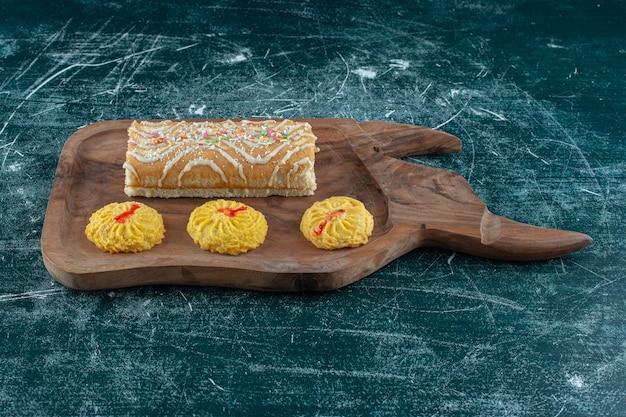 青いテーブルの上に、ボード上のクッキーとロールケーキ。