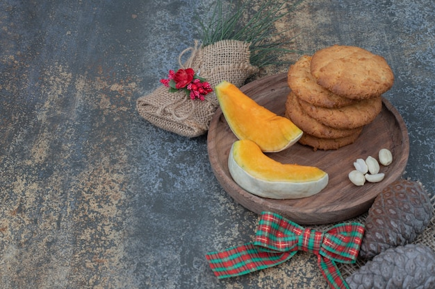 Печенье и кусочки тыквы на деревянной тарелке, украшенной лентой. фото высокого качества