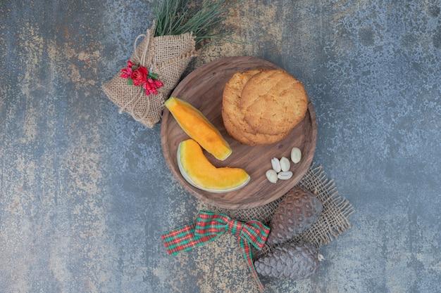 リボンで飾られた木の板にカボチャのクッキーとスライス。高品質の写真
