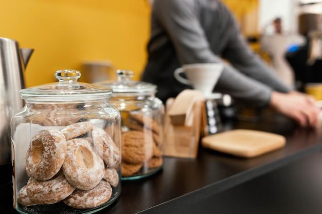 초점이 흐려진 남성 바리 스타와 함께 커피 숍 카운터의 쿠키와 간식