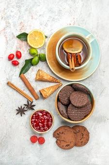 Biscotti i biscotti appetitosi una tazza di tè con bastoncini di cannella al limone e marmellata
