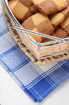 Cookies in a basket on the table with a blue cloth