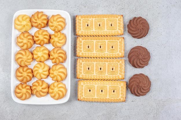 Biscotti e biscotti allineati in un piatto e su una superficie di marmo.
