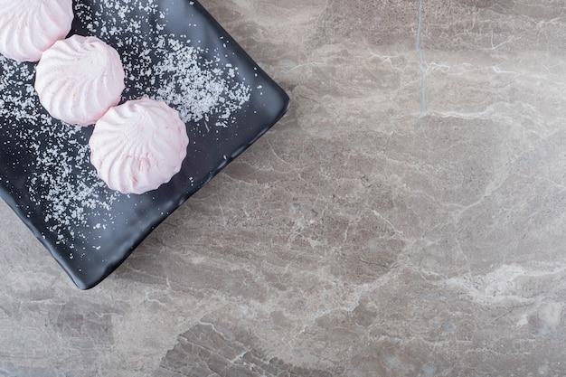 Biscotti su un piatto nero su superficie di marmo