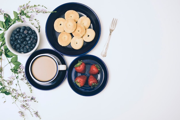 Cookies; blueberries; coffee and strawberries on white backdrop