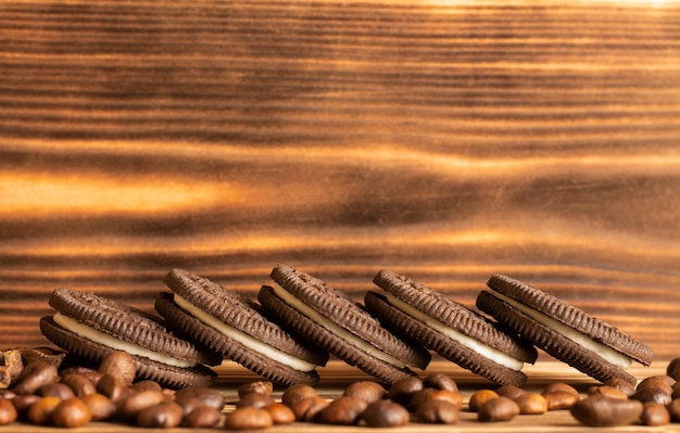 Cookies on a brown table of a burnt tree with coffee grains scattered on the table.