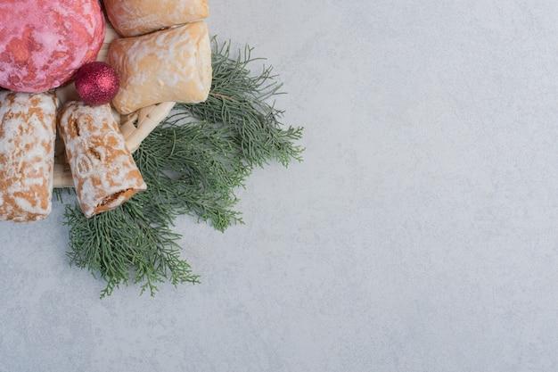 Biscotti impacchettati in un cestino bianco su un mucchio di rami di pino