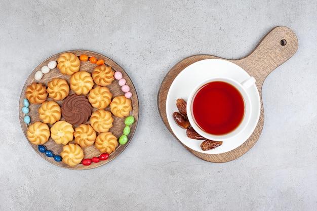 대리석 표면의 나무 판자에 날짜가 있는 쿠키, 사탕, 차 한 잔.
