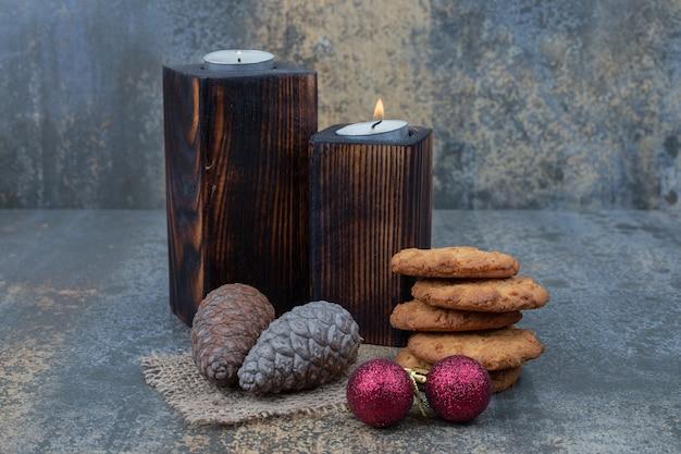 大理石のテーブルにクッキー、キャンドル、光沢のあるボール、松ぼっくり。高品質の写真