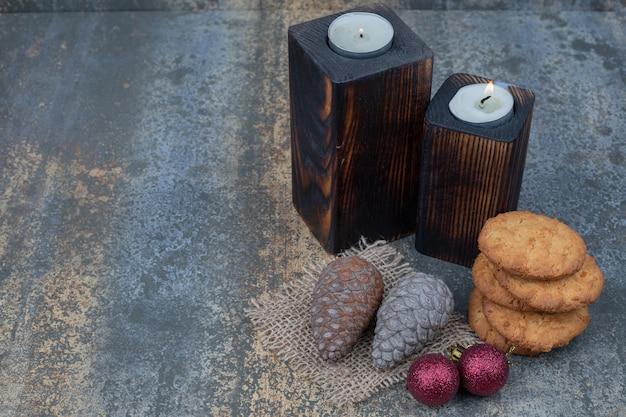 대리석 테이블에 쿠키, 양초, 반짝이 공 및 솔방울. 고품질 사진