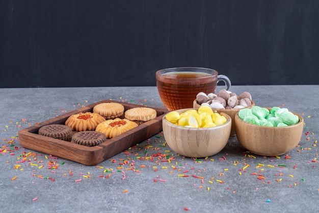 Biscotti, ciotole di caramelle e una tazza di tè