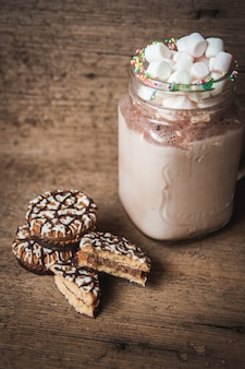 Cookies in chocolate and a bottle of cocoa with marshmallows