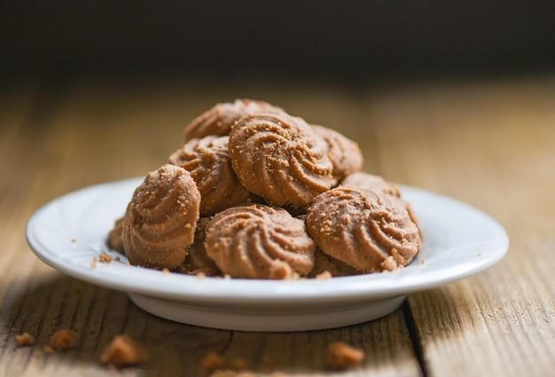 白いプレートと木製のテーブルにクッキーチョコレート、ミニクッキービスケット