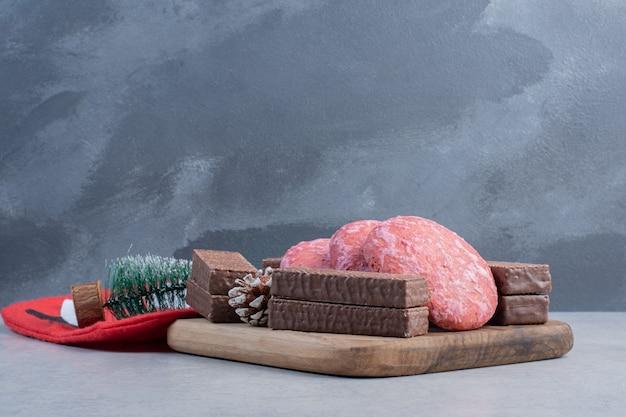 Biscotti, wafer al cioccolato e ornamenti natalizi sulla superficie in marmo