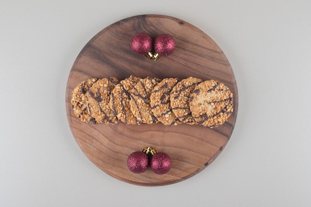 Cookies and christmas baubles on a wooden board on white background.