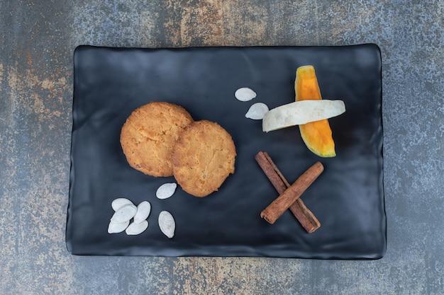 黒いプレートにクッキー、シナモン、カボチャのスライス。高品質の写真