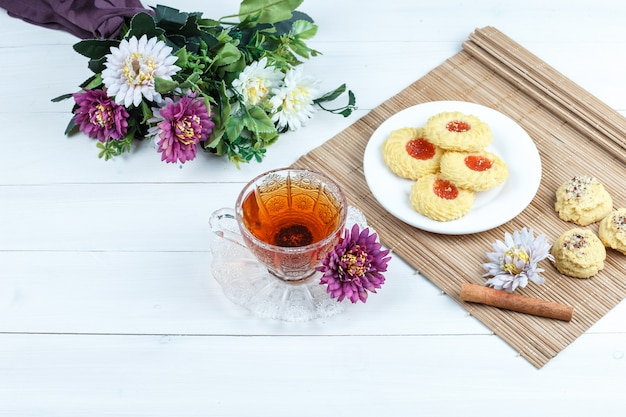 Cookies, cinnamon on a placemat with flowers, cup of tea high angle view on a white wooden board background