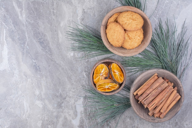 Cookies, cinnamon sticks and orange slices in wooden cups