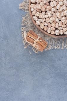 Biscotti e bastoncini di cannella sull'asciugamano, sullo sfondo di marmo.