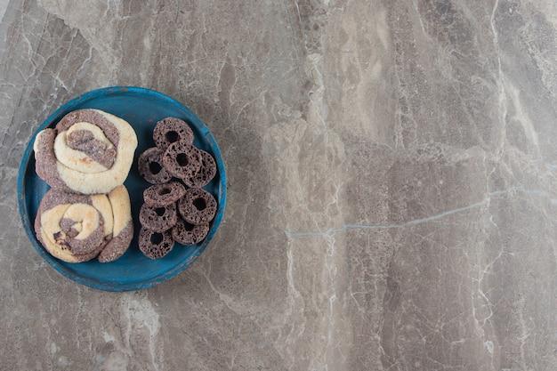 Biscotti e anelli di mais su un piatto di legno su marmo.