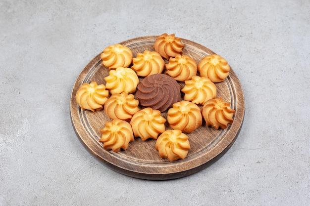 Печенье декоративно выровнено на деревянной доске на мраморном фоне. фото высокого качества