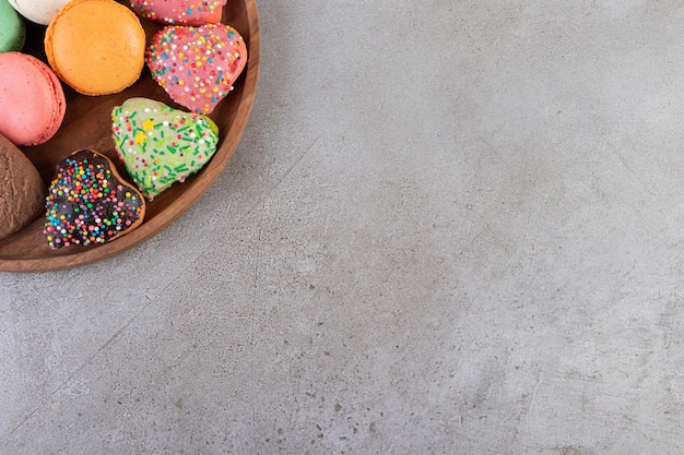 Cookies in a different shape on wooden tray over grey background.
