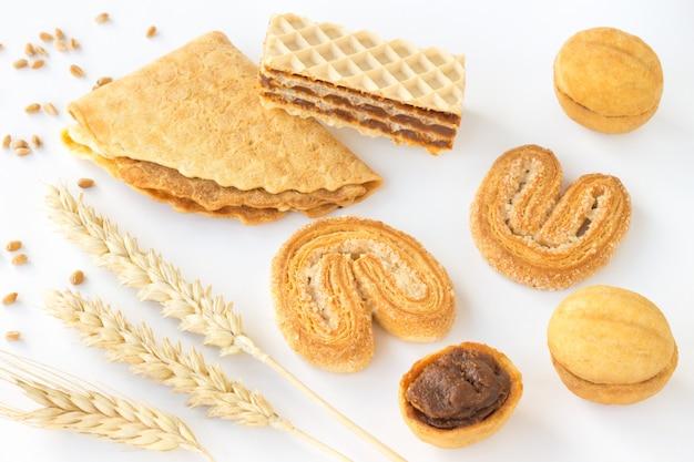 さまざまな種類のクッキーと白いテーブルに小麦のスパイク