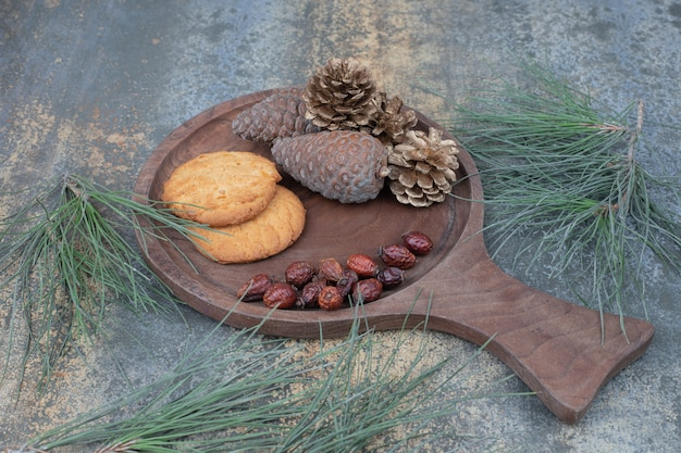 木の板にクッキー、乾燥ローズヒップ、松ぼっくり。高品質の写真