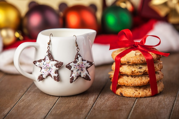 Cookies, earrings and christmas gifts at background