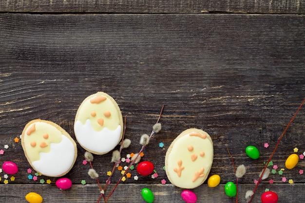 나무 테이블에 쿠키 부활절 달걀과 설탕 과자 뿌리