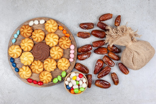 Biscotti circondati da caramelle su una tavola di legno accanto a una ciotola di caramelle, un sacco e datteri sparsi sulla superficie di marmo.