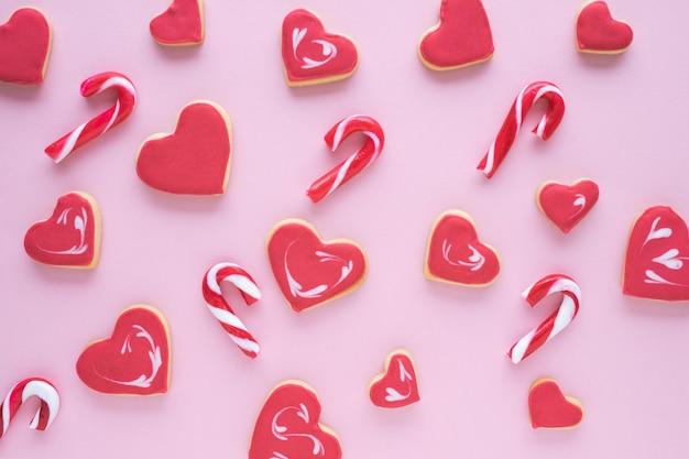 ピンクの背景にクリスマスのさまざまな形のクッキー。フラットレイ。