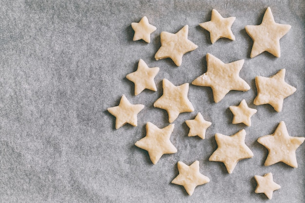 Cookies in the form of stars on parchment paper lies in baking tray, holiday pastries, christmas cookies