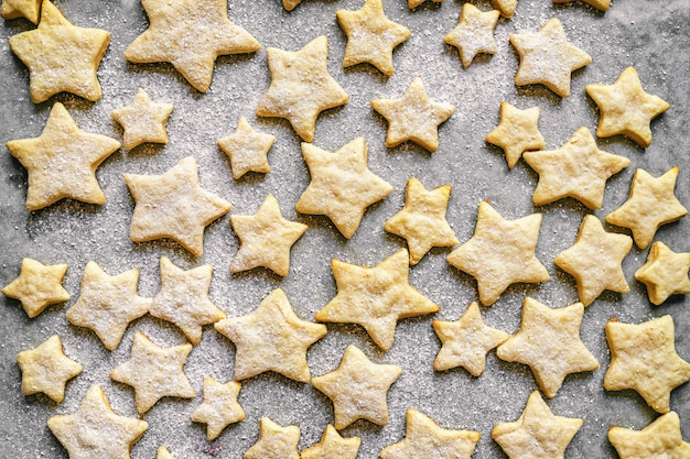 Cookies in the form of stars sprinkled with powdered sugar on parchment paper lies in a baking tray, holiday pastries, christmas cookies