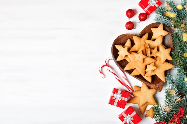 Cookies, gifts and fir-tree branches on a white wooden table