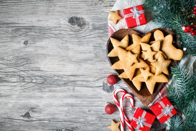 Cookies, gifts and fir-tree branches on a wooden table.