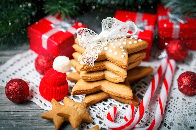 Cookies gifts and fir tree branches on a wooden table.