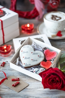 Cookies or gingerbread cookies in a gift box with a red ribbon on a wooden table. valentine's day.