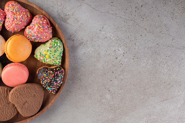 Cookies in heart shaped with sprinkles placed on a stone table.